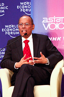 A middle-aged Indian man wearing a black suit, white shirt and red tie speaking into a microphone.