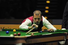 Photograph of Barry Hawkins with a cue and a rest.