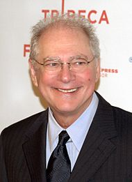 A white-haired man wearing glasses and a suit smiles and looks off-screen.