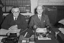 Two men sit side by side at a desk.