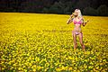 Blond woman in a pink underwear on a field with yellow flowers 02.jpg