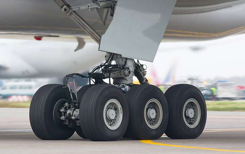 Aircraft landing gear. Six wheel gear on the ground, with attachment assembly and gear door leading up to the aircraft belly.