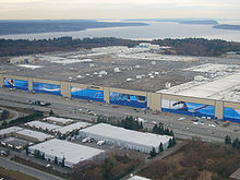An aerial view of Boeing's Everett Plant, where the Boeing 767s undergo final assembly. In the mid-ground is the building's giant doors are covered with pictures of the company's products. This is set against a tranquil background of a river banked by trees.