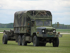 M35 series 2½-ton 6x6 cargo truck - Bombardier MLVW licensed version of M35, with C3 howitzer in tow