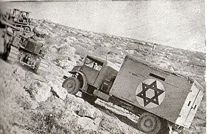 "Sha'ar HaGai - A bulldozer tows a truck on the ""Burma Road"" to Jerusalem, June 1948"