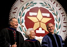 "The head and shoulders of three people - an older man, an older woman, and a middle-aged man - wearing formal robes are shown in front of a large circular seal. On the outer edges of the seal the letters ""XAS A...IVERSITY...87..."" are visible; an inner band of leaves separates the letters from a block T superimposed with a star."