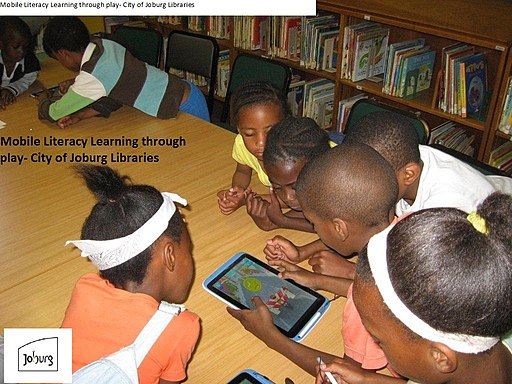 CHILDREN USING TABLETS TO PLAY GAMES AND AND READ STORIES AT RABBI RIDGE LIBRARYJOBURG SOUTH AFRICA
