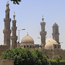 Exterior view of al-Azhar Mosque. Four minarets and three domes visible