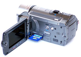 AVCHD - Canon HF100 camcorder with a partially inserted Secure Digital card.
