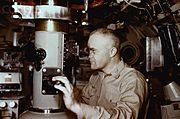 Captain Edward L. Beach dressed in khaki uniform gazing through the viewfinder while adjusting the focus using dial control on the periscope in the conning tower of the nuclear submarine USS Triton