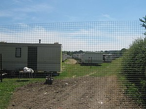 Migrant education - This large field is filled with mobile homes. Temporary accommodation for many migrant workers working on the acres of orchards of Selling Court Farm.