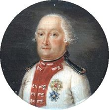 Middle aged man, plump, wearing formal tie and white jacket, with military decorations.