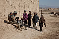 Children gather around a member of the Afghan National Civil Order Police providing security in the Maiwand district, Kandahar province, Afghanistan, Feb 120225-A-QD683-051.jpg