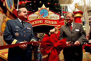 Macerich - Lt.-Gen. Rick Findley, deputy commander of the North American Aerospace Defense Command, and Robert Taylor, senior property manager at Citadel Mall, perform the ceremonial ribbon cutting during the Nov. 18, 2005 launch of the Citadel Mall's Santa Tracking Station.