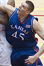 A Caucasian basketball player in a Kansas #45 jersey is boxing out.