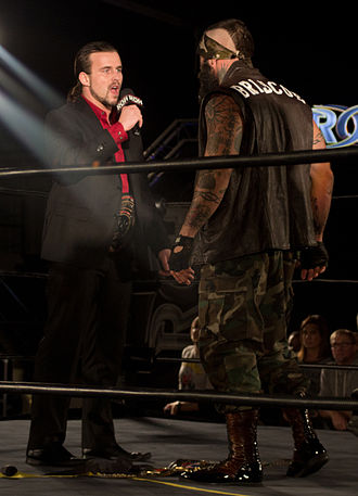 Jay Briscoe - Jay Briscoe confronting Adam Cole over which of them is the real ROH World Champion; Briscoe's title belt is on the floor between them, while Cole is wearing his.