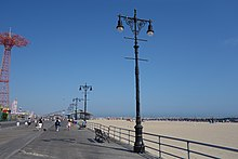 Original street lights, similar to those installed on Fifth Avenue in Manhattan. They consist of stylized black poles with two lamps at the top. The boardwalk is on the left and the beach is on the right.