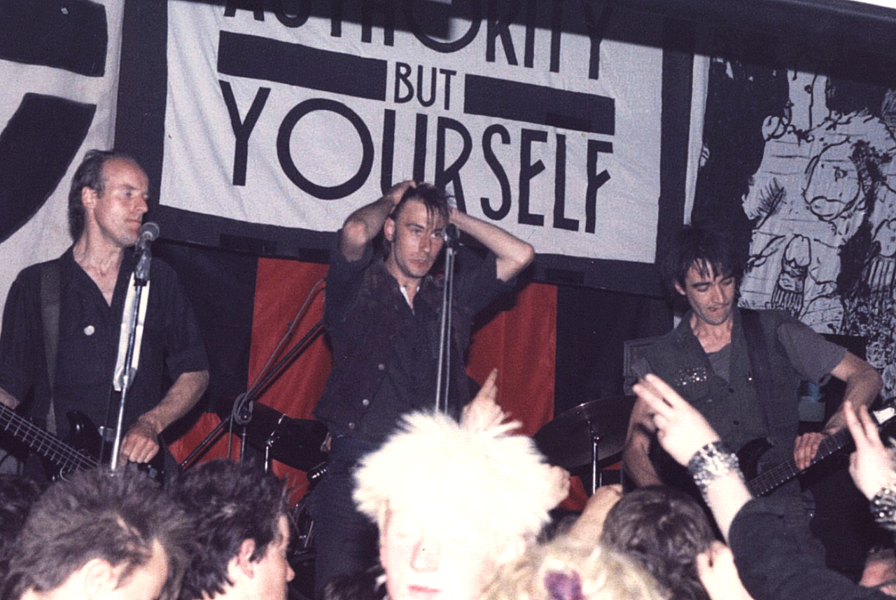 """Crass on stage in Cumbria in May 1984, with the slogan """"there is no authority but yourself"""" in the background. From left to right: Pete Wright, Steve Ignorant, and N.A. Palmer."""