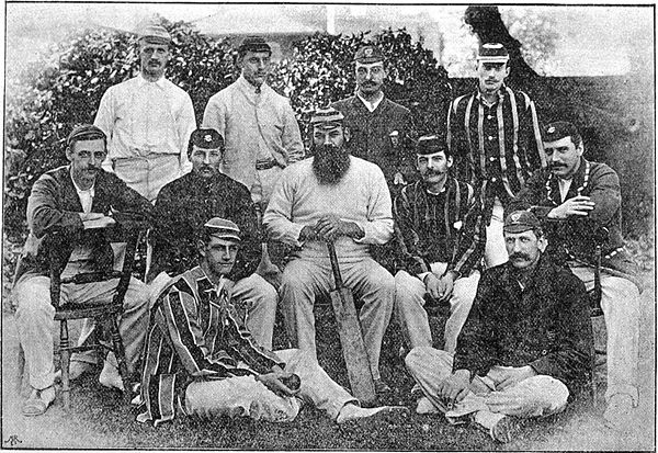 11 men dressed in cricket clothing posing for a group photograph. Three rows.