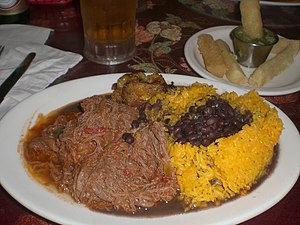 Cuban cuisine - Ropa vieja (shredded flank steak in a tomato sauce base), black beans, yellow rice, plantains and fried yuca with beer