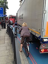 Lorry stands on blue-painted road; cyclist is between lorry and pavement with railings.