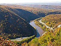 Aerial view of a river turning between rolling hills with forests in fall colors