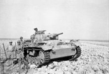 A tank lies crippled in the desert with soldiers standing around it