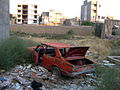 Destroyed red car in a abandoned zone nearnear amin eslami garden- Nishapur 7.JPG