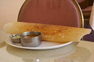 A plate of Dosa with chutney and sambhar