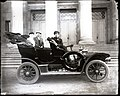Driver and passengers in an early automobile.jpg