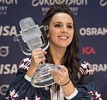 Photograph of Jamala holding the Eurovision trophy: a glass structure shaped to look like a retro microphone from the 1950s