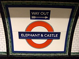 "A London Underground ""roundel"" reads ""Elephant and Castle."" A smaller sign says ""Way Out"" above it."