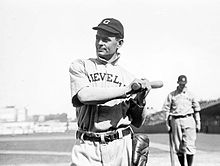 "A black-and-white photo of a man in a white baseball uniform with ""CLEVELAND"" across the chest and a dark baseball cap with ""C"" on the face in white; he is holding a baseball bat over his left shoulder"
