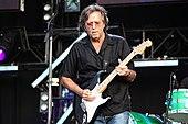 Un homme sur une scène portant un jean bleu, une chemise noire et des lunettes.  Il tient une guitare noire, et une partie d'une batterie et d'autres équipements audio et de scène peuvent être vus en arrière-plan.
