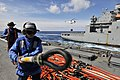 Flickr - Official U.S. Navy Imagery - Sailors aboard USS Whidbey Island carry a cargo net hooking pole on the ship's flight deck during a vertical replenishment.jpg