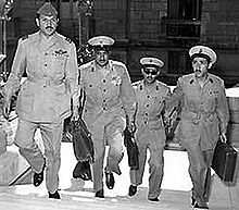 Four men in military uniform, wearing buttoned jackets, wide-rimmed hats, black shoes, and carrying briefcases. They are ascending the stairs of a building.