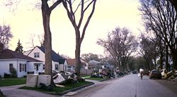 A neighborhood with piles of damaged possessions located in front of many homes. The piles included a washer and dryer, mattresses, and furniture. A man can be seen riding a bike down the middle of the street.