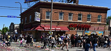 Corner store near site of Floyd's death with crowd of protesters