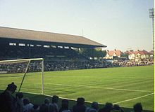 A colour photograph, taken from behind a goal net, of a roofed English-style grandstand, filled with people
