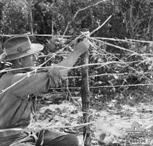 A man in a slouch hat adjusts what looks like barbed wire.