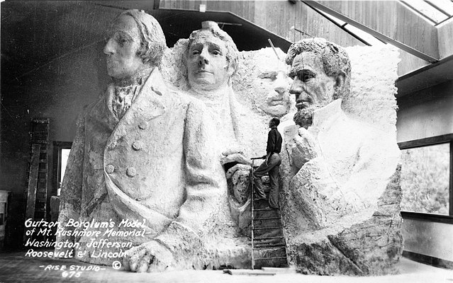Gutzon Borglum, Mount Rushmore sculptor, stands next to model for Mount Rushmore