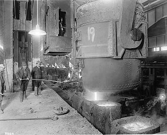 Homestead Steel Works - Steel workers gaze on as molten steel is poured from ladle to casts at Homestead Steel Works.