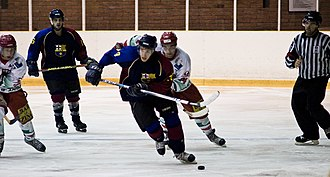 FC Barcelona Ice Hockey - A Barcelona player carries the puck with two opposing players in chase.