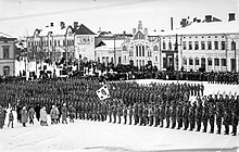 A parade of Finnish Jägers at the Vaasa town square. Spectators are gathered around the soldiers in the background. General Mannerheim is inspecting the formation in the foreground.
