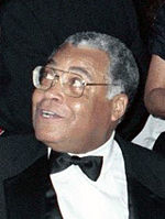 A smiling black-skinned man in a suit