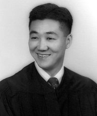 Head and shoulders of a young man with a bright smile and neatly combed hair wearing what appears to be a graduation gown over a shirt and tie.