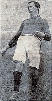 A black and white photograph of a man wearing a dark coloured football shirt and white shorts.