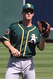 "A man wearing a green baseball jersey with yellow and white trim with a white ""A"" on the left chest, a green cap, and sunglasses, stands holding his brown baseball glove out awaiting to catch a ball."