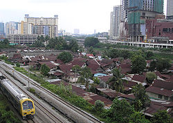 The northern half of Kampung Haji Abdullah Hukum (as of August 2007), as seen from the Abdullah Hukum LRT station and with the incomplete Gardens shopping centre to the right. By 2008, much of the village was cleared away for a further expansion of the Mid Valley City development project.