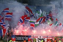 A large number of supporters, waving flags, displaying banners and setting off flares.